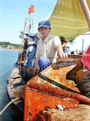 Chủ tàu Trần Văn Quang và chiếc mỏ neo bị tàu lạ đâm lút vào mũi tàu. Ảnh: Đức Nguyễn.