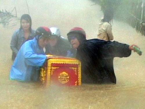 Gia đình 2 người bị chết do lốc xoáy ở Quảng Sơn, H.Quảng Trạch, Quảng Bình đưa quan tài người chết đi tránh lũ - Ảnh: Trường Giang