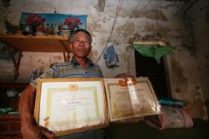 Ông Hào trong căn nhà rách nát cùng giấy tờ 30 năm tuổi Đảng của bố và bằng công nhận liệt sĩ của mình.