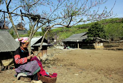 Phụ nữ người Mông ngồi thêu trước hiên nhà.
