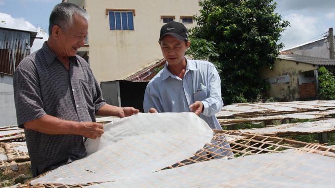 Ông Huỳnh Tài Phúc (trái) kiểm tra độ ẩm của bánh hủ tiếu trước khi đem cắt thành sợi