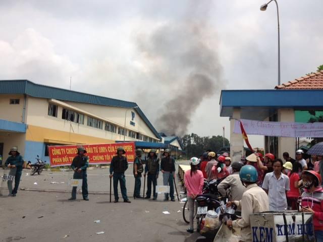 Công nhân lo lắng, bảo vệ cố gắng chặn cửa công ty Chutex, Sngapore, trong khi khói vẫn bốc lên từ một nhà xưởng bị cháy.