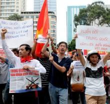 """11-5-2014, biểu tình tại Sài Gòn chống Trung Quốc đưa giàn khoan HD 981 vào vùng biển Việt Nam. Người bên góc trái là """"ông hội đồng"""" Đặng Văn Khoa, cầm cờ là Osin Huy Đức. Ảnh Hương Trà"""
