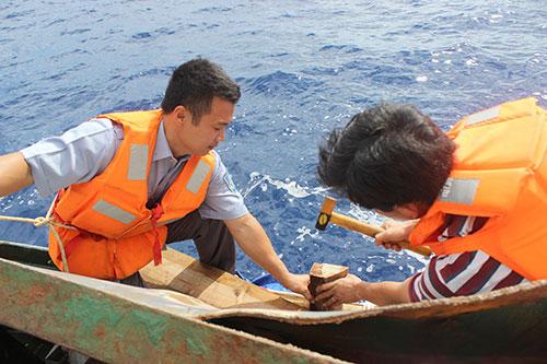 Các kiểm ngư viên tàu 951 gia cố những vết thủng ở ngay khoang máy chính mạn trái tàu