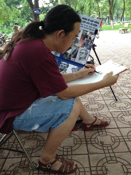 Nhà báo Etcetera Nguyễn đi đôi dép mà các chiến sĩ Cảnh sát biển Việt Nam tặng trong chuyến tác nghiệp tại Hoàng Sa. Trong ảnh, ông đang ngồi ký họa bên hồ Gươm - Hà Nội ngày 5/6. (Ảnh: Tuấn Hợp).