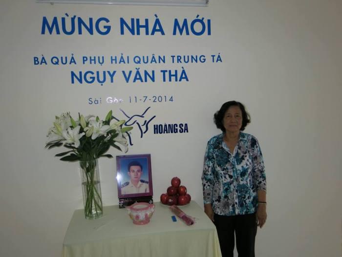 Bà Huỳnh Thị Sinh với bàn thờ chồng trong căn nhà mới. Ảnh Nguyễn Thông