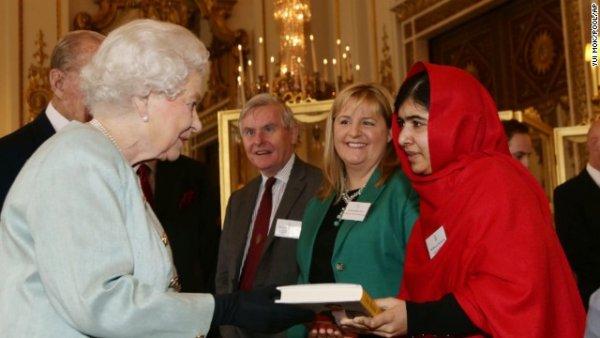 Malala trao tặng nữ hoàng Anh Elizabeth II cuốn sách của cô trong buổi tiệc chiêu đãi ở cung điện Buckingham vào tháng Mười năm 2013.