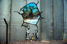 """Những đứa trẻ Palestine lớn lên trong những vùng đất bị Israel phong tỏa hết các đường ra biển, sẽ """"nghịch cát"""" như thế này đây, trong một tác phẩm của họa sĩ đường phố Banksy vẽ trên tường vây quanh khu định cư Palestine"""