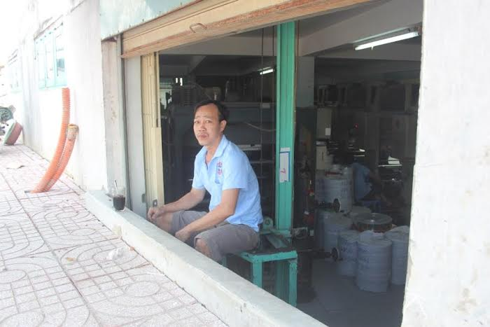 Nhà thấp hơn so với mặt đường. Trong ảnh một công nhân đang ngồi uống cà phê như đang ngồi trong quán bar.